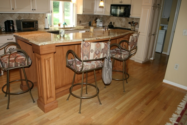 Two level island with stained distressed finish with painted cabinets with overlay doors